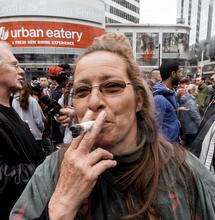 an old lady smoking a big fatty joint in the middle of a crowd.