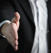 business man offering a handshake.