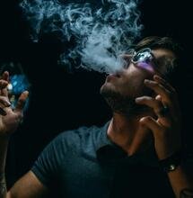 young man releasing a fume out of his mouth.