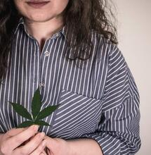 woman holding leaf of marijuana.