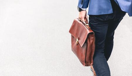 man holding a brown leather bag.