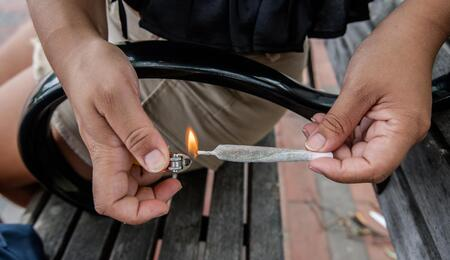 young man lighting up a nicely rolled joint.